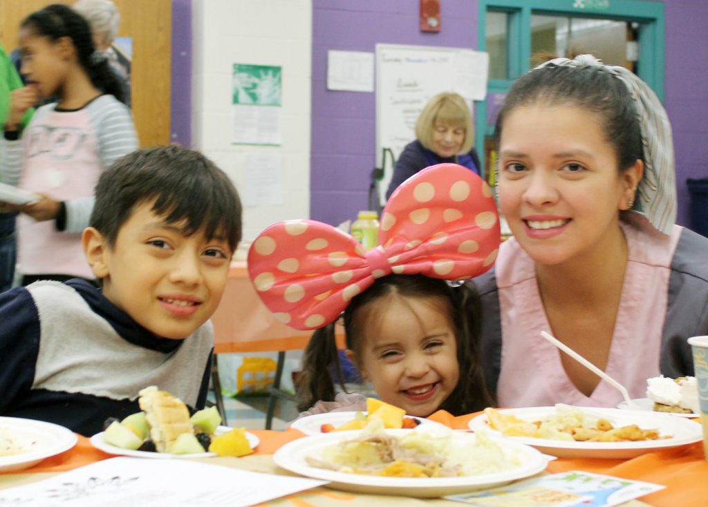 Family enjoying a meal at Thanksgiving Potluck
